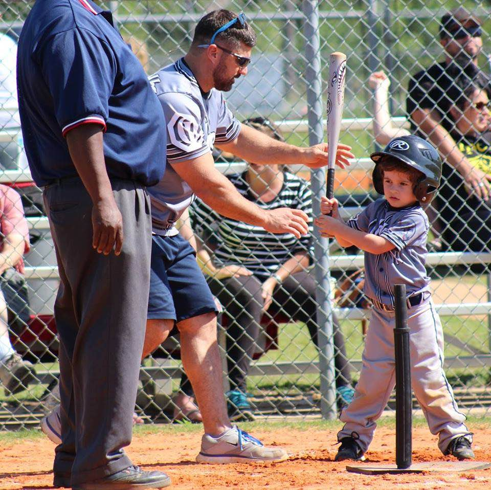A child playing t-ball.