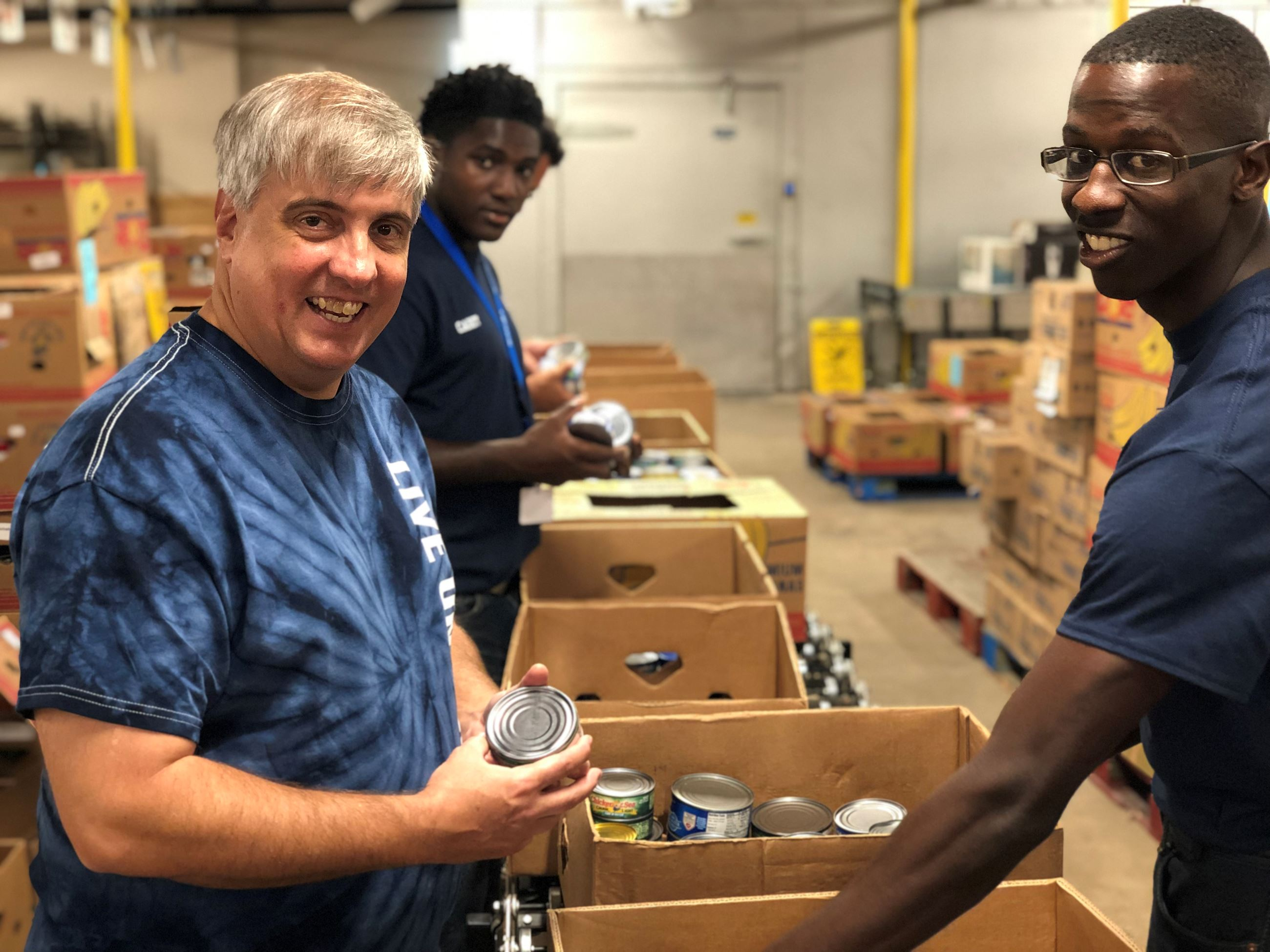 Mayor Grover Robinson and city staff sort cans at Manna Food Pantries