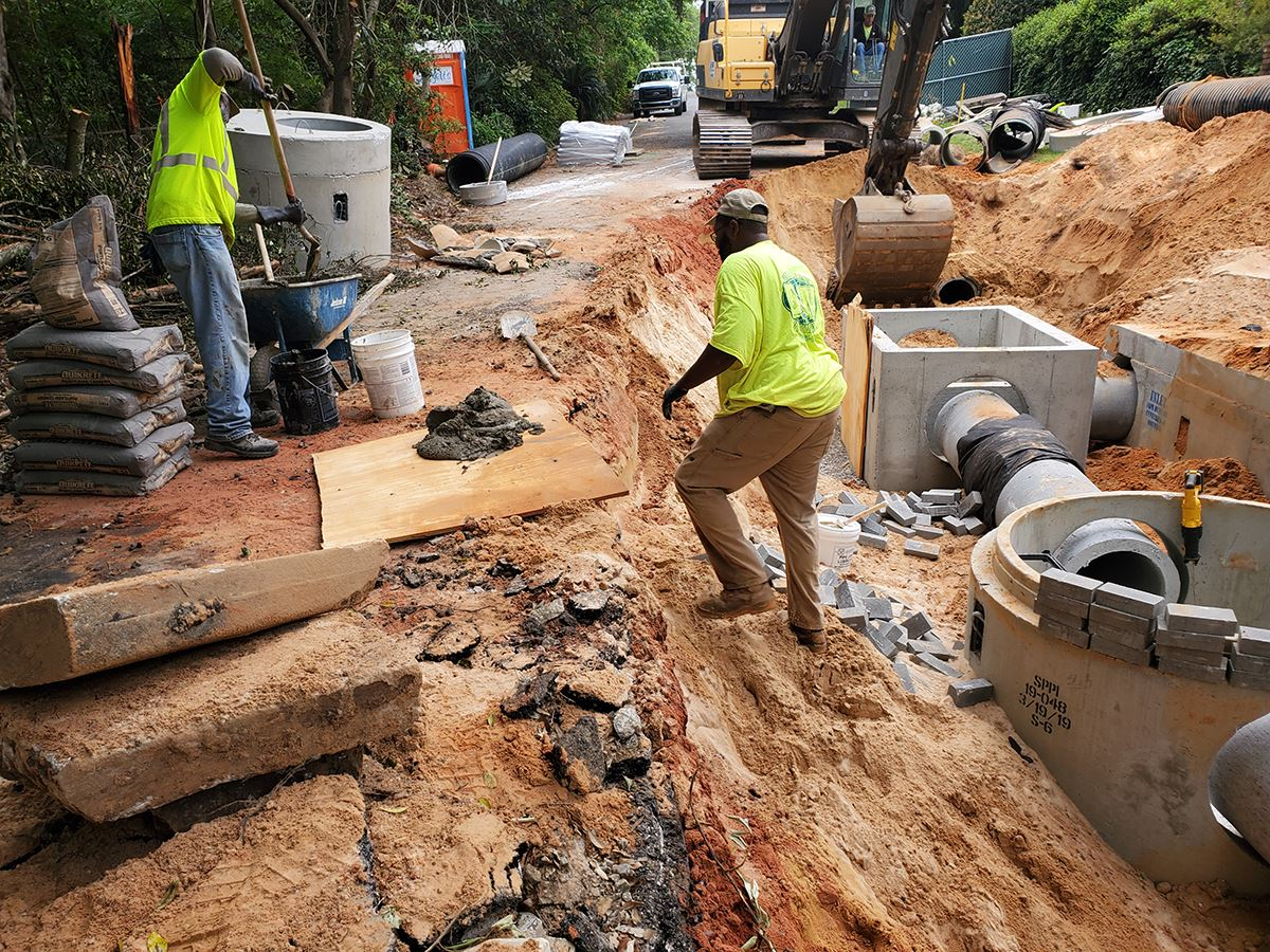 Construction workers install an underground stormwater treatment unit