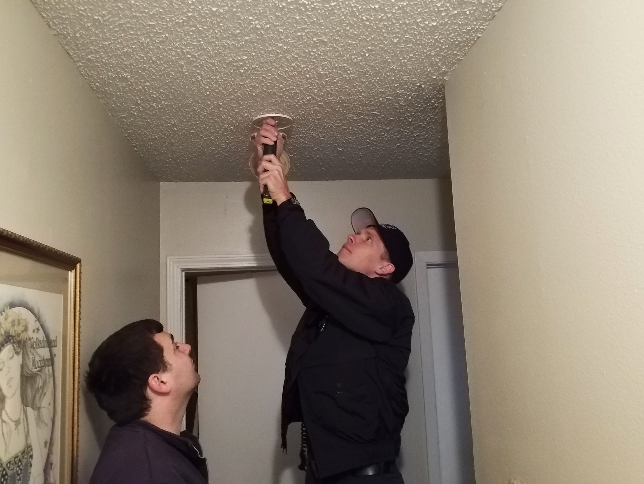 Two firefighters install a smoke alarm in a home