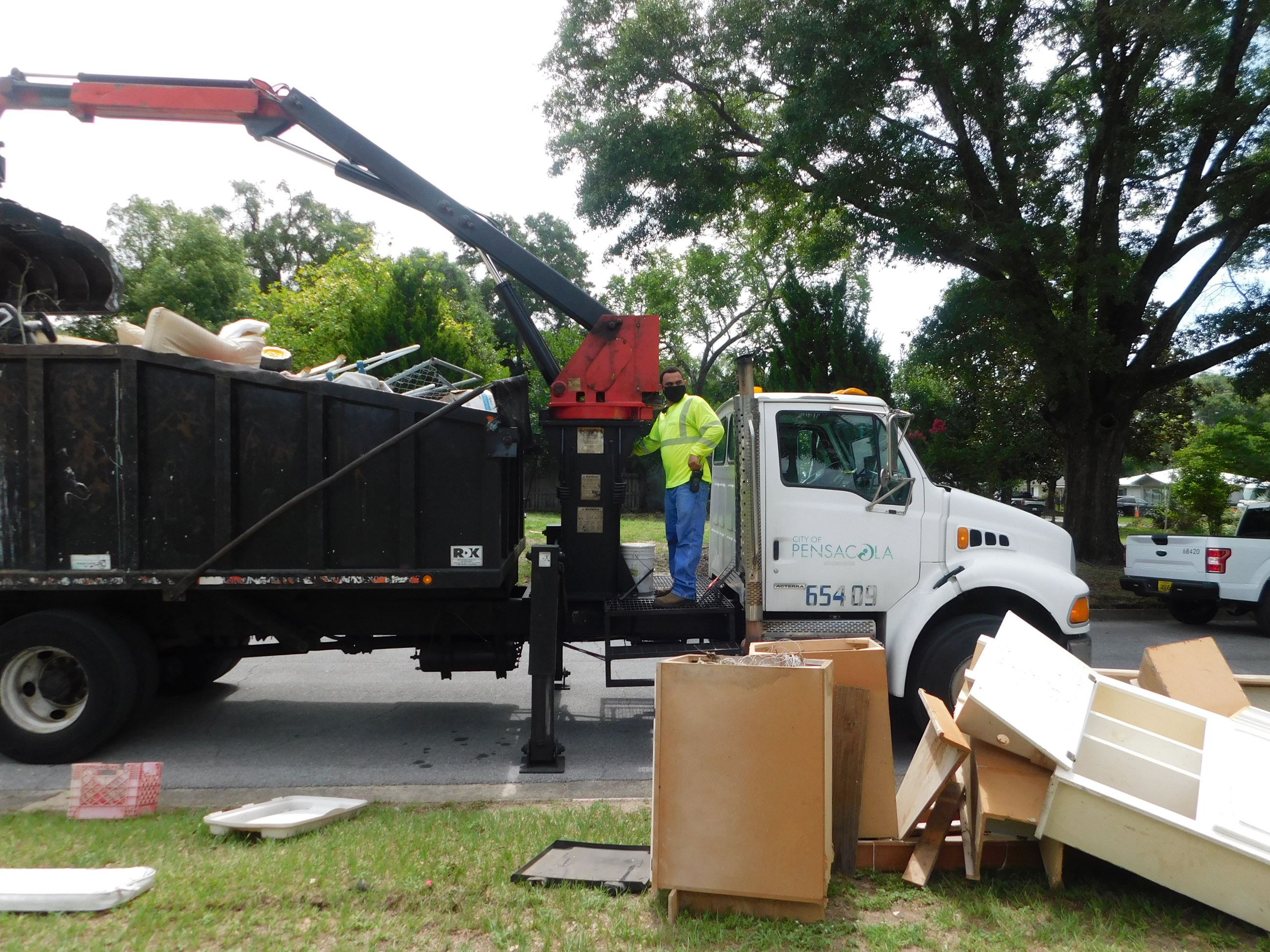 A city sanitation worker on a truck picks up debris during the mayor's neighborhood cleanup