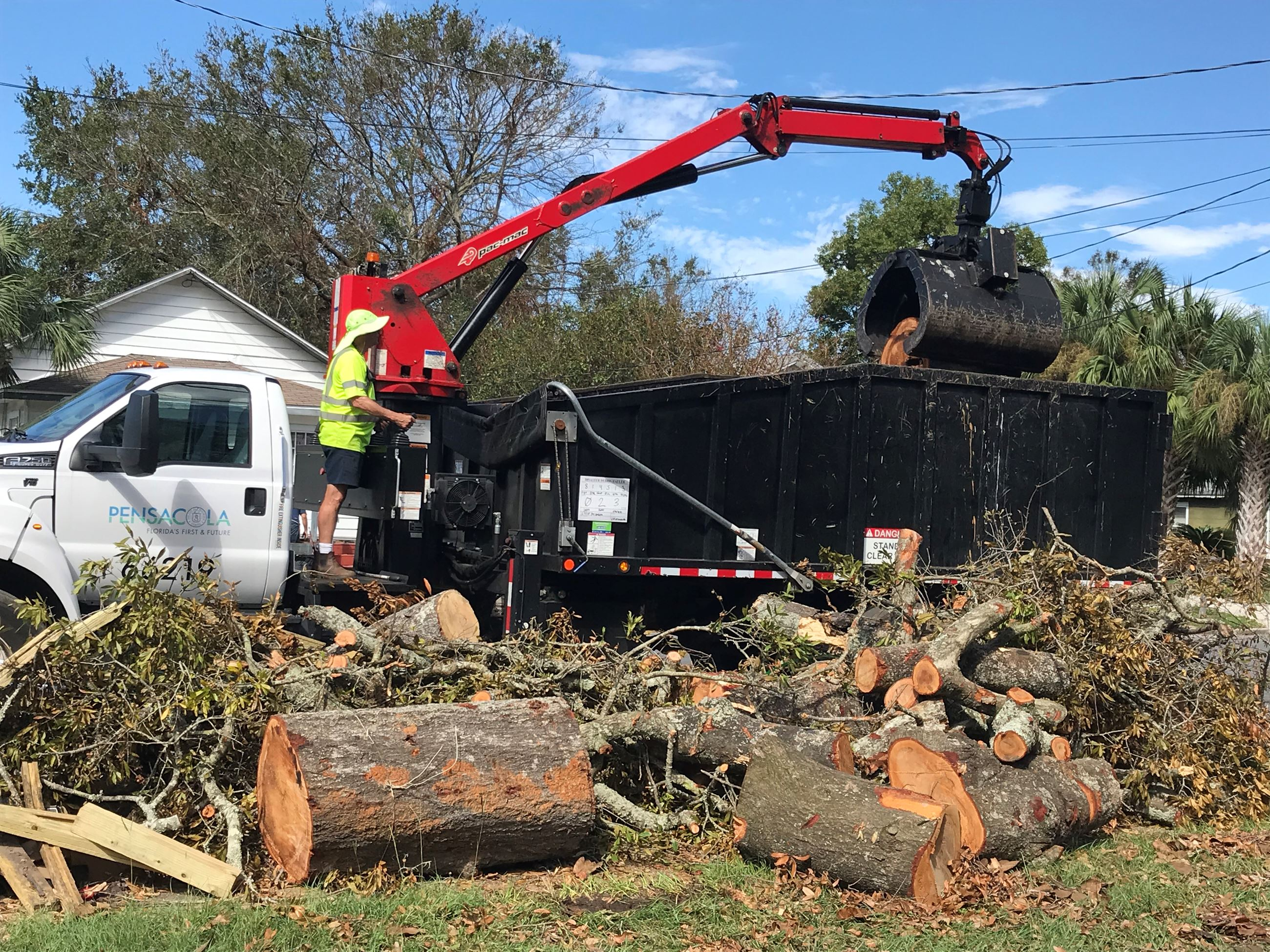 A city sanitation worker collects yard debris